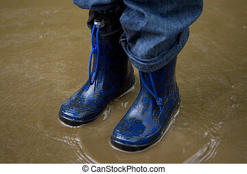 Standing In a Muddy Puddle - A little boy in blue boots...