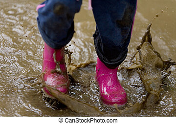 Splash! - A little girls pink boots splashing in a muddy...