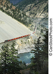 Freight train going through mountain area and near river. BC...