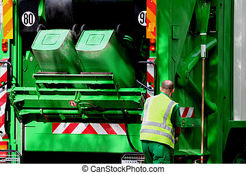 Garbage truck and blue collar worker in the street