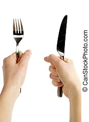 Knife and Fork - A knife and fork being held by womans...