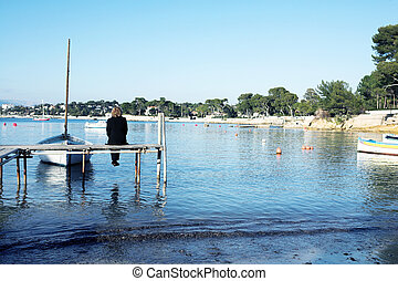 Antibes #261 - A person sitting on a pier in Antibes,...