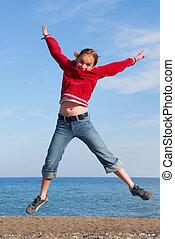 Girl jumping on a beach