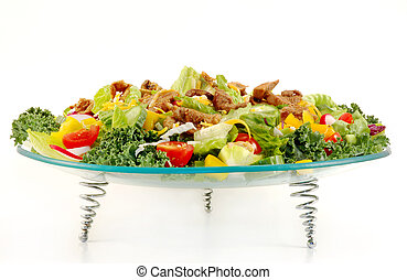 Mixed green salad with beef meat presented on a glass plate