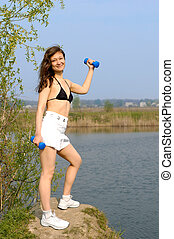 Young woman with weights exercising outdoors