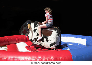 Bull riding - Little girl trying her skill at staying on the...