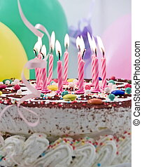 Birthday cake with eleven burning candles, balloons at...