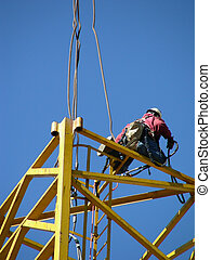 Kneeling High - Construction worker kneeling on a scaffold...