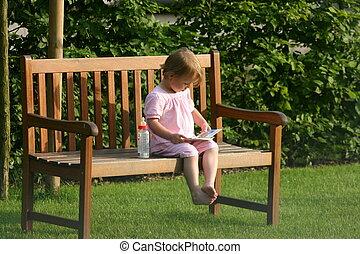 little bookworm - little girl enjoying the evening sun, her...