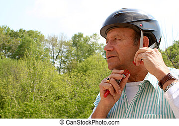 senior helmet - older gentleman puts on safety helmet for a...
