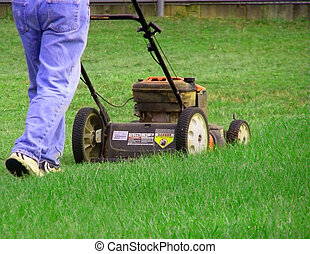 Man Mowing Yard - Man using push mower to cut lawn
