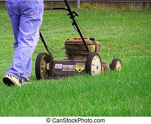 Man Mowing Yard - Man using push mower to cut lawn