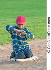 watching first base - little boy bored sitting on first base