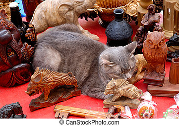 Cute funny gray cat sleeping among antique decor objects -...