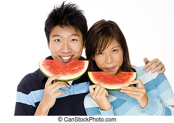 Taking A Bite - A young asian couple eating watermelon
