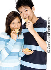 Eating Chips - A young chinese couple eating chips