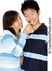 Feeding Him - A cute young asian woman feeds her man a chip