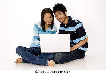 Couple using Laptop - A young asian couple sitting on the...