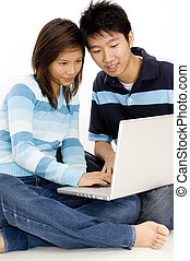 Technology Together - A happy young couple sitting on floor...