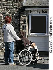 Committed Helper - Elderly female in a wheelchair being...