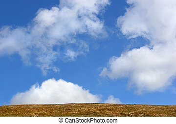 Sky and Earth - Barren grass hillside against a blue sky...
