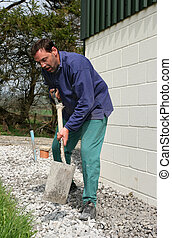 Man With A Spade - Man with a spade shovelling and levelling...