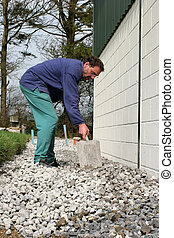 Levelling Gravel - Man with a spade shovelling and levelling...