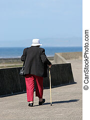 Keeping Fit - Elderly female with a walking stick, walking...