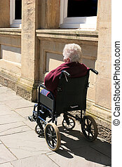 Waiting for Help - Disabled elderly female sitting in a...