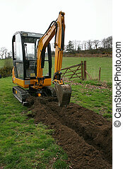 Trench Digger - Mini digger standing in a field next to a...