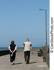 Leisurely Stroll - Elderly man and woman walking along a...