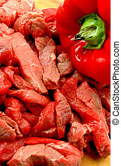 BEEF STRIPS - beef strips and red pepper on cutting board