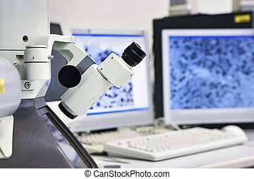 microscope in front of two screens