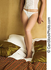 Lingerie#254 - Woman in underwear standing on a bed.