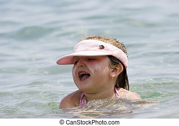 Protection from sun  - Girl in water with sunscreen and hat