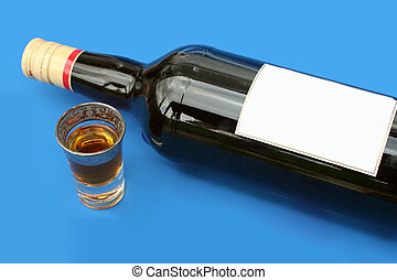 drinking alone - alcohol bottle with blank label and shot...