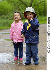 Sharing A Puddle - A little boy and girl wearing wellington...