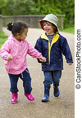 Running In The Park - A little boy and girl wearing...