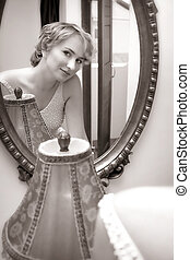 Bride looking in a mirror - Reflection of a young woman in...