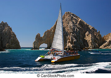 Sailing at Cabo - A catamaran sails past the Los Arcos rock...