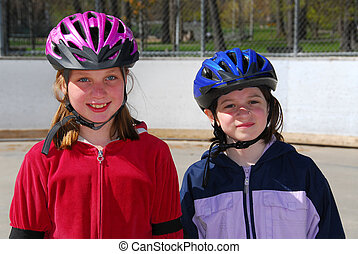 Two girls rollerblading - Two happy girls rollerblading in...