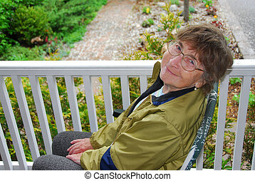 Senior woman smiling - Senior woman sitting on a porch and...