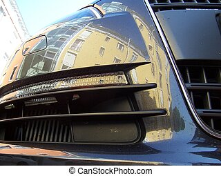 audi vs. city - building mirrored in a audi\\\'s mudguard