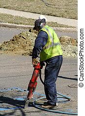 Jackhammerer - Worker using a jackhammer on asphalt street.