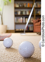 Putting practice in the home - Golfer with putter rehearsing...