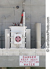 hydroelectric power - transformer at dam with sign warning...