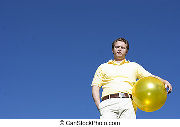 Man standing under blue sky - Man in a yellow shirt holding...