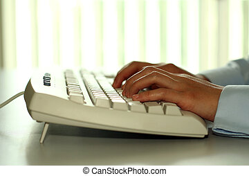 Typing on a keyboard - A business person typing on a...