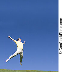 Jumping free - Man jumping free outside in a blue sky with...