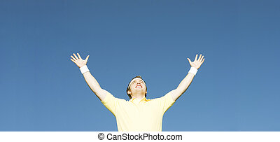 Success Man - Man raises his arms in victory under a blue...
